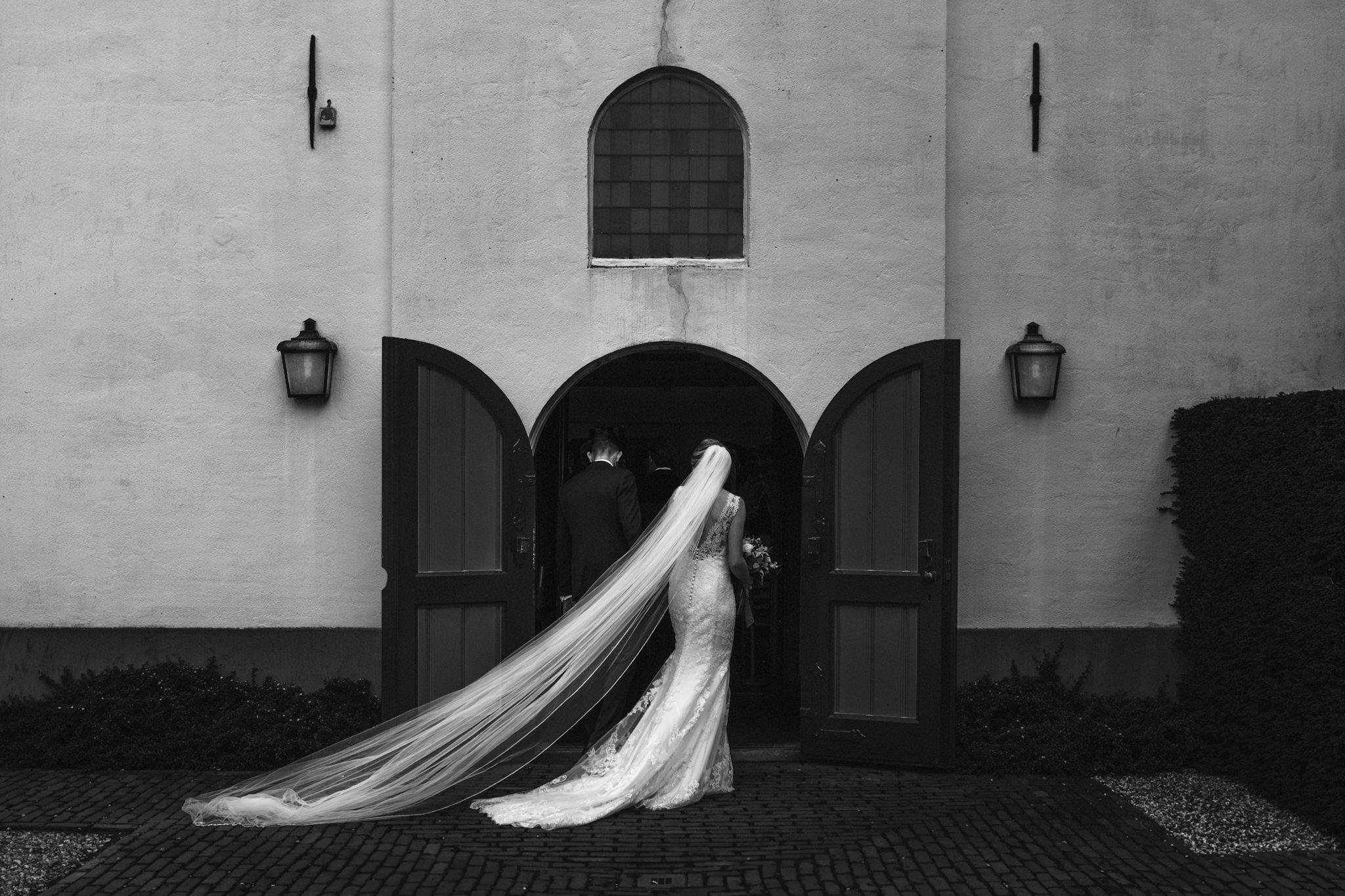 De sluier van een bruid hangt sierlijk op de grond terwijl ze met haar vader de ceremonie betreed