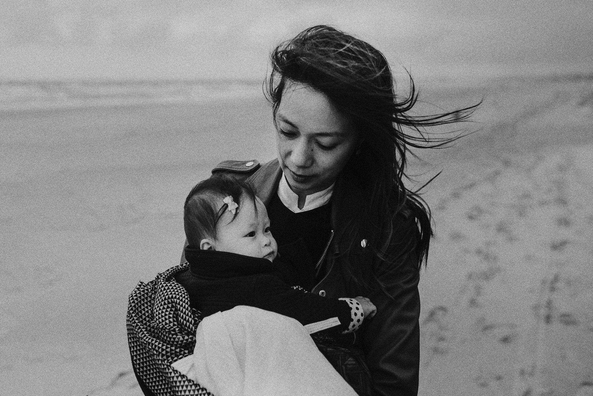 Portret van moeder en kind wandelend op het strand