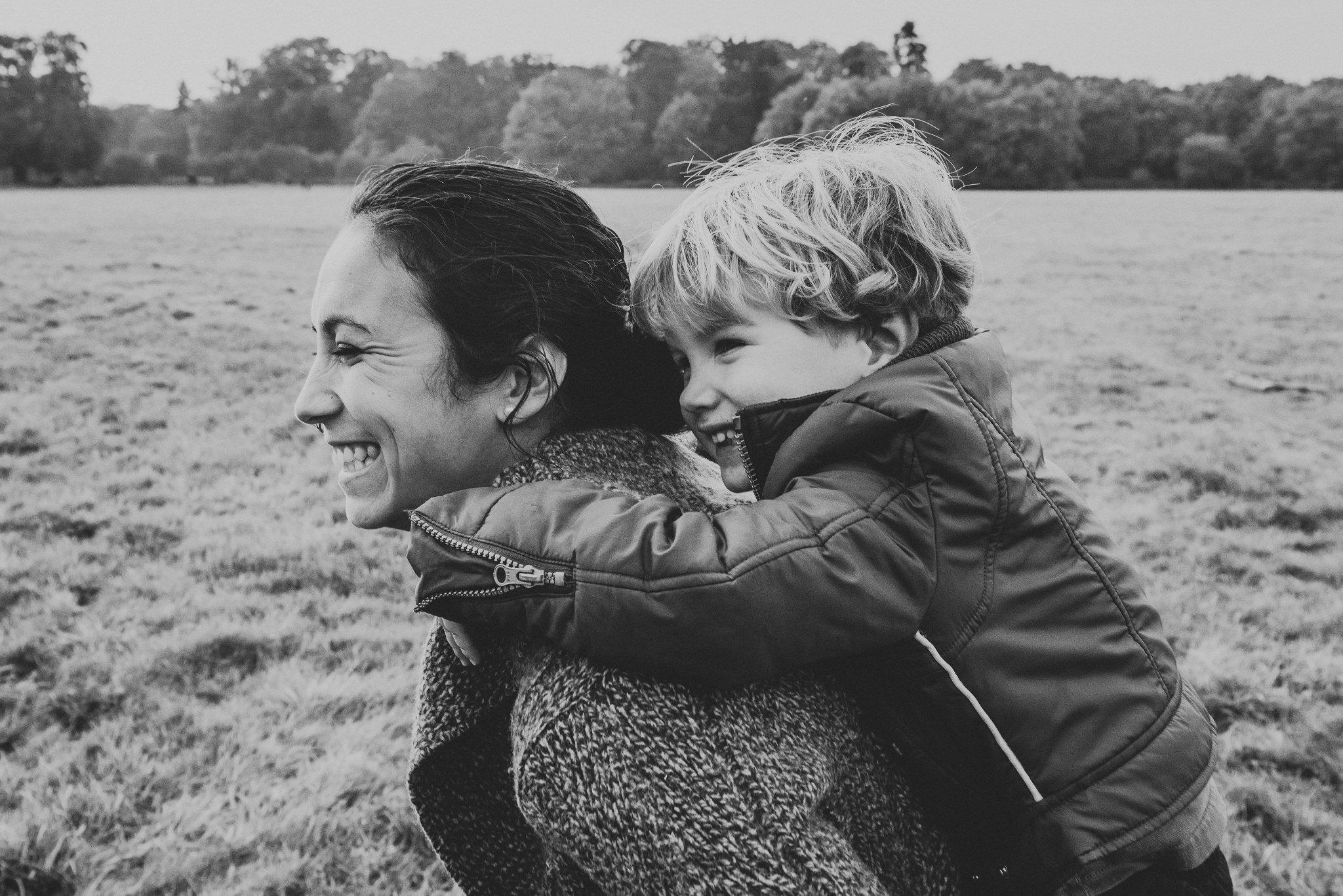 moeder houdt haar zoon vast terwijl zij door een landschap wandelen tijdens een familieshoot