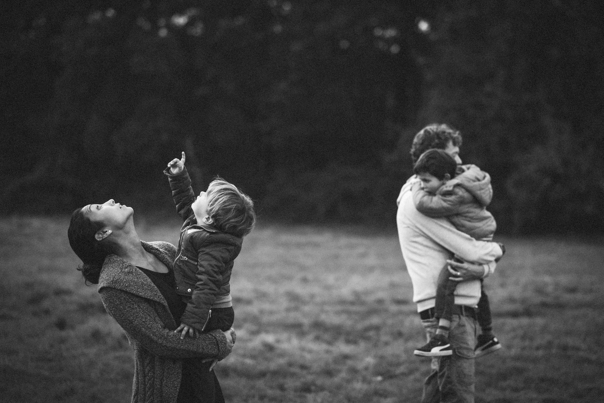 Een familie loopt tijdens een familie fotoshoot over een mooi landschap