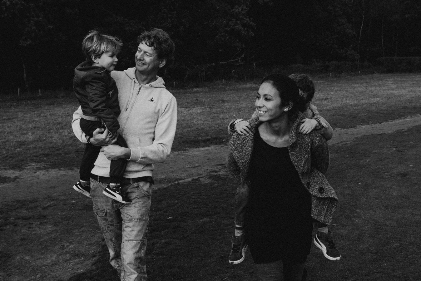 zwart wit foto van een familie loopt met een hondtijdens een familie fotoshoot over een mooi landschap