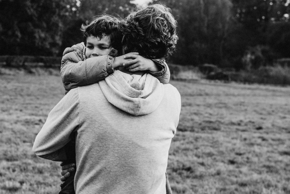 vader houdt zijn zoon vast terwijl zij door een landschap wandelen tijdens een familieshoot