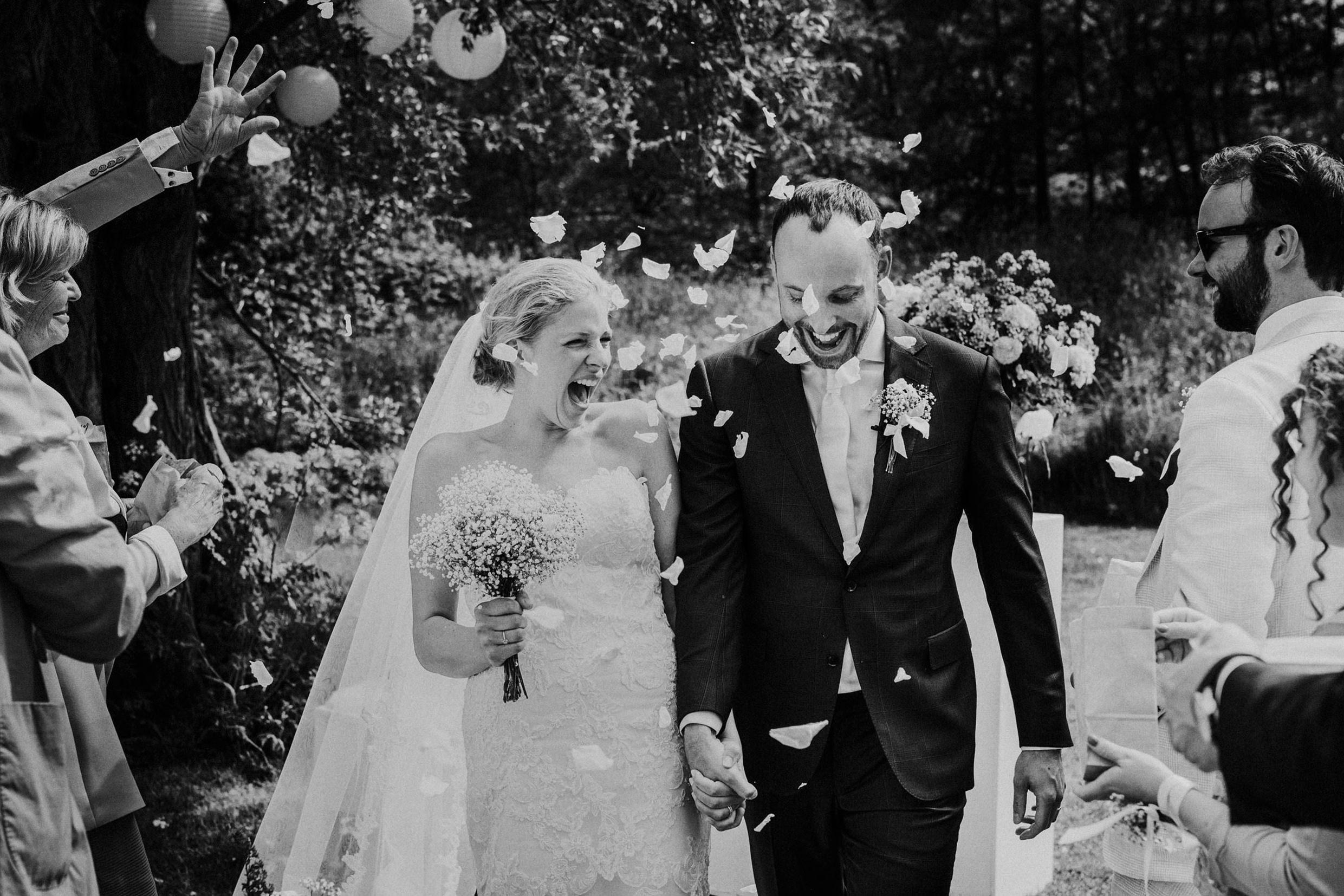 bruidspaar loopt dolgelukkig door haag van rozenblaadjes op paviljoen puur